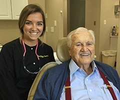 Team member and smile senior man in dental exam chair