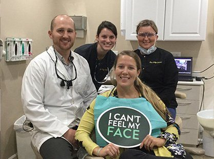 Dentist team members and smiling patient in dental exam room