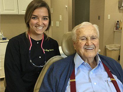 Team member and smiling senior dental patient