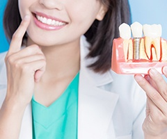 A woman holding a mold with a dental implant and pointing to her teeth