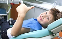 Smiling child in dental chair giving thumbs up