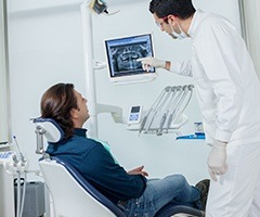 Dentist and patient looking at dental x-rays