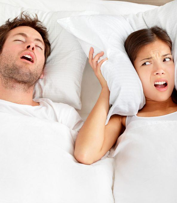 man snoring and woman holding pillow over her ears