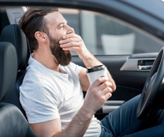 A man yawning in his car while holding coffee.