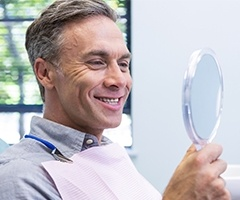man smiling into dental mirror