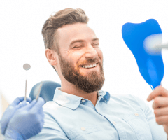 Man in dental chair looking at smile