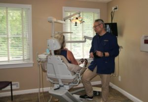 A dentist speaking with a patient.