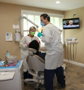 Two dentists helping a patient.