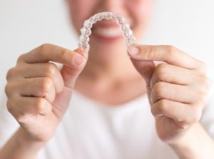 Smiling woman holds Invisalign in Charlottesville in front of her