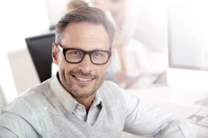 Confident businessman with glasses smiling